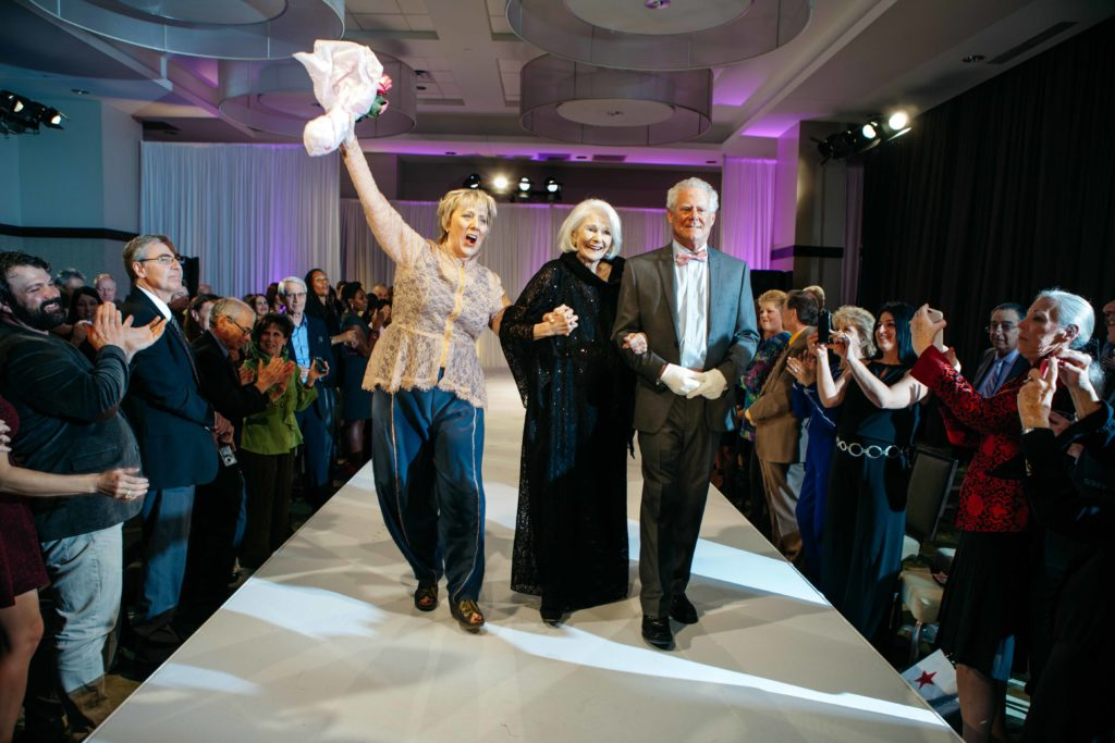 Triumphant as survivors on the runway! Sue Miller and I at the Sue Miller Day of Caring fashion show 2016. Photo by Hardy Klahold.