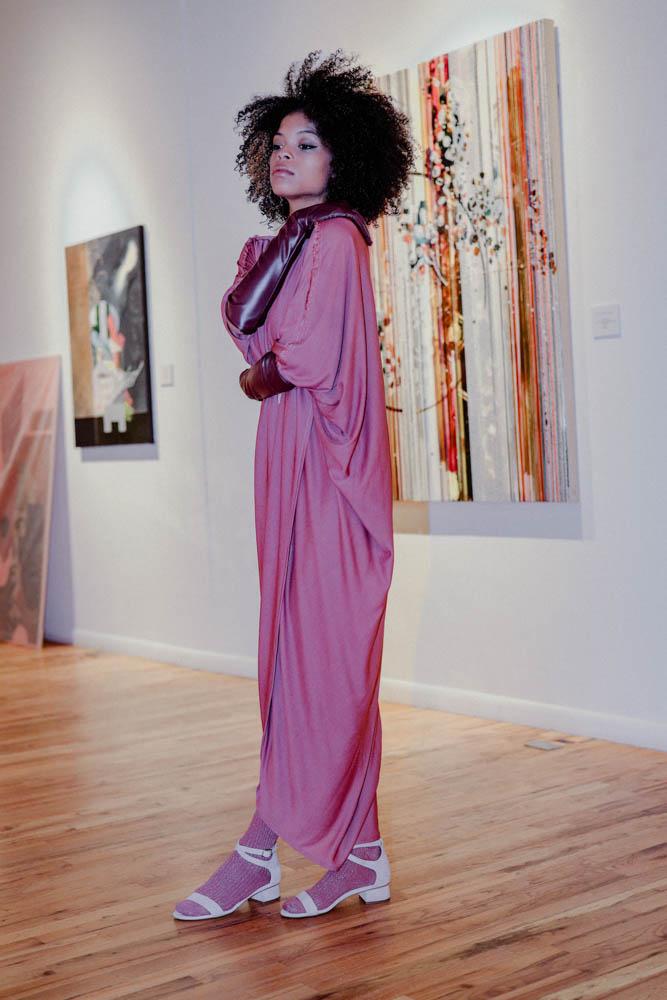 DanShay in a draped jersey dress in front of art by Nina Tichava.